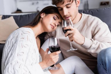 Brunette woman holding glass of wine near boyfriend at home stock vector