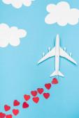 Draufsicht auf Flugzeugmodell und rote Herzen auf blauem Hintergrund mit weißen Wolken
