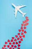 Draufsicht auf Flugzeugmodell und rote Herzen auf blauem Hintergrund