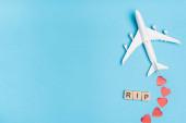 Draufsicht auf Flugzeugmodell, Wortbruch und rote Herzen auf blauem Hintergrund
