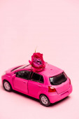 toy car and red rose on pink background