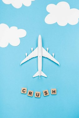 Top view of plane model and cubes with word crush on blue sky background stock vector