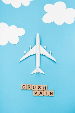 Top view of plane model and cubes with word crush pain on blue sky background stock vector