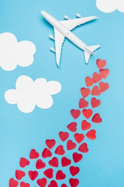 Top view of plane model and red hearts on blue background with white clouds stock vector
