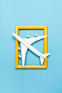 Top view of white plane model and empty frame on blue background stock vector