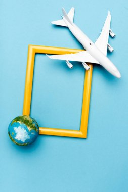 Top view of white plane model, globe and empty frame on blue background stock vector