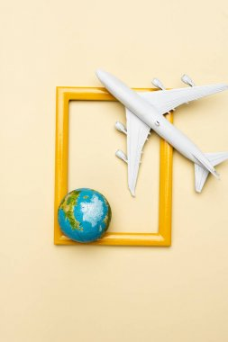 Top view of white plane model, globe and empty frame on yellow background stock vector
