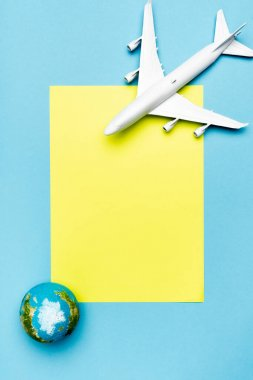 Top view of white plane model, globe and empty yellow paper on blue background stock vector