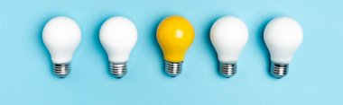 Top view of white and yellow light bulbs on blue background, banner stock vector