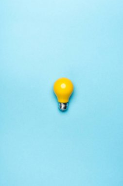Top view yellow light bulb on blue background stock vector