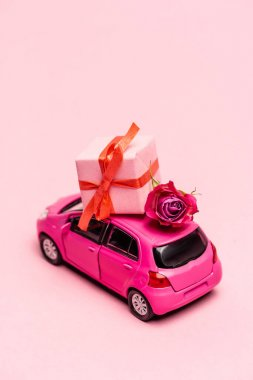 Toy car and gift box with rose on pink background stock vector