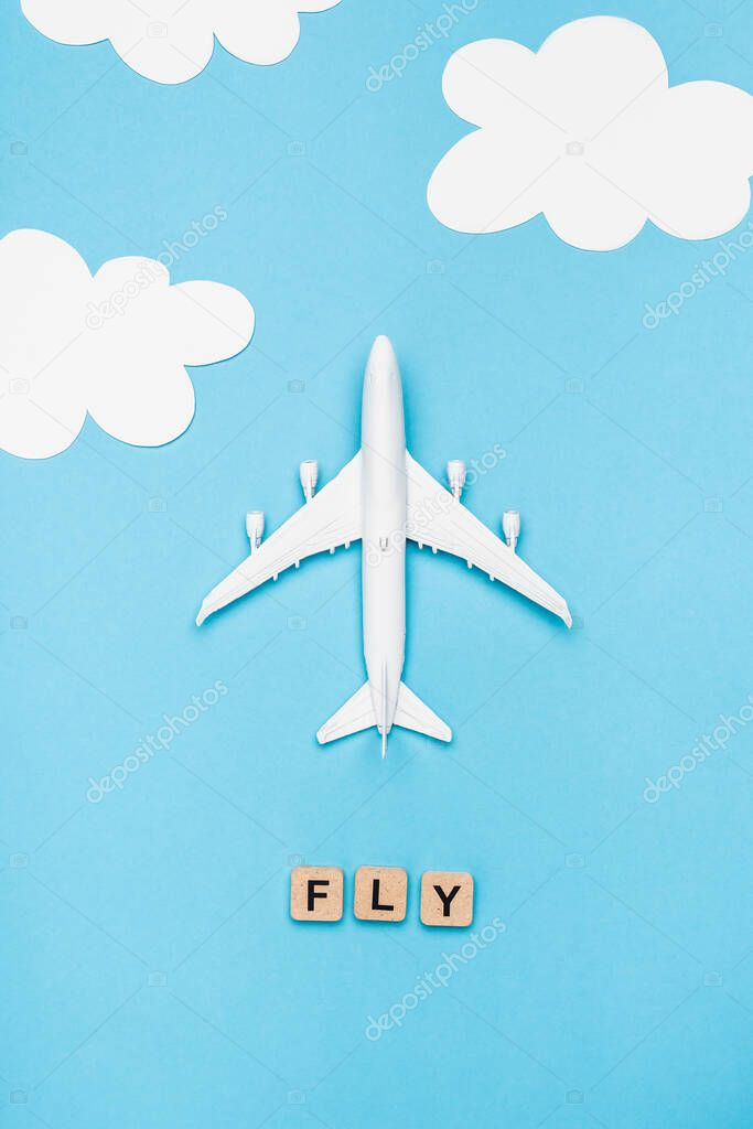 Top view of plane model and cubes with word fly on blue sky background stock vector