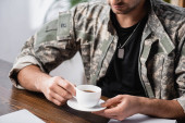 cropped view of military man in uniform holding cup of coffee and saucer in office