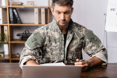 Soldier in uniform sitting at desk and using laptop stock vector