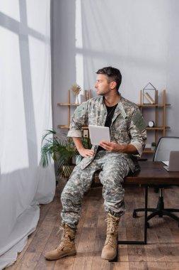 Soldier in military uniform holding digital tablet near laptop on desk stock vector