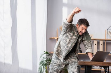 Excited military man with clenched fist rejoicing while using laptop stock vector