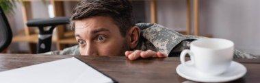 Scared military man hiding under desk, banner stock vector
