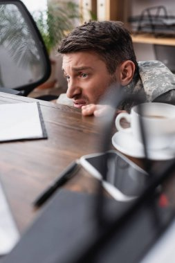 Displeased military man hiding under desk with cup of coffee and smartphone stock vector