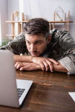 Upset military man in uniform looking at laptop on desk stock vector