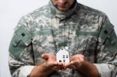 dům model v rukou vlasteneckého vojáka v uniformě na rozmazaném pozadí izolované na bílém