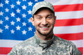 happy military man in uniform and cap smiling near american flag on blurred background