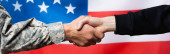 cropped view of soldier shaking hand with civilian man near american flag on blurred background, banner