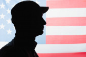 side view of patriotic military man in uniform and cap near american flag on background