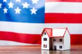 dům model na dřevěném stole v blízkosti americké vlajky na rozmazaném pozadí