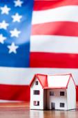 dům model v blízkosti americké vlajky na rozmazaném pozadí
