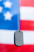 Photo close up of blank silver badge on chain near american flag on blurred background