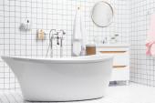 Interiér bílé koupelny s vanou a toaletními potřebami