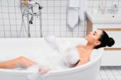 Bruneta žena ležící se zavřenýma očima ve vaně s pěnou