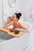 Sexy Frau lächelt, während sie Erdbeere in der Nähe von Glas Champagner auf Badewanne Tablett essen