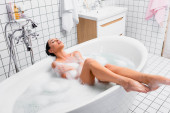Young woman relaxing with closed eyes while sitting in bathtub with lather