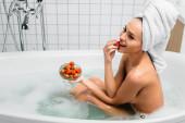 Sexy Frau im Handtuch auf dem Kopf isst Erdbeere in Badewanne mit Schaum