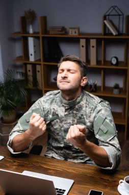 Excited military man in uniform sitting with clenched fists while rejoicing near laptop and smartphone on desk stock vector
