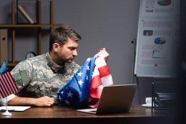 Sad military man in uniform holding flag of america near laptop stock vector