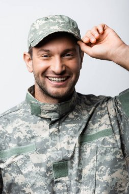 Happy military man in uniform fixing cap isolated on white stock vector