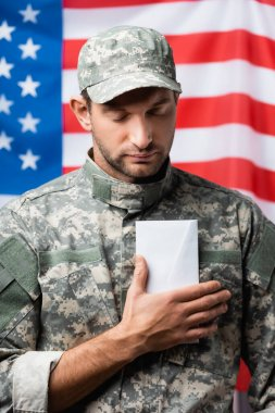 Patriotic military man in uniform and cap holding envelope near american flag on blurred background stock vector