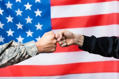 Cropped view of soldier fist bumping with civilian man near american flag on blurred background stock vector