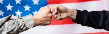 Cropped view of soldier fist bumping with civilian man near american flag on blurred background, banner stock vector