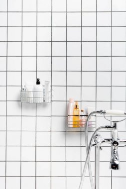 Toiletries near faucet on blurred foreground in modern white bathroom stock vector