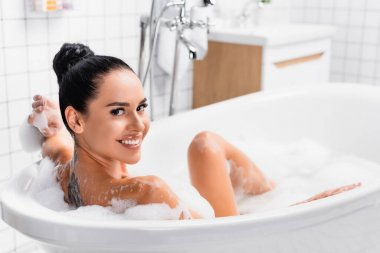 Tattooed woman smiling at camera while taking bath on blurred background stock vector
