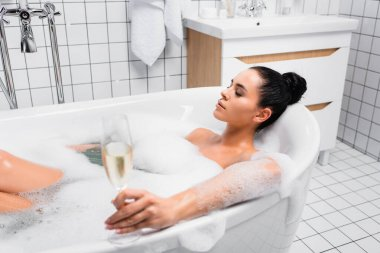 Young woman with closed eyes holding glass of champagne on blurred foreground while taking bath stock vector