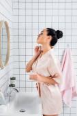Mladá žena v hedvábí župan použití kosmetické sérum v blízkosti zrcadla v koupelně