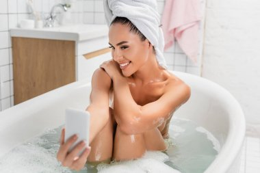 Cheerful woman taking selfie on smartphone on blurred foreground in bathroom stock vector