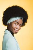usmívající se africká americká mladá žena v modrém stylovém oblečení izolované na žluté