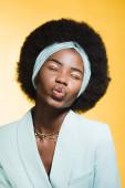 africký americký mladý žena v modrém stylový outfit ukazující polibek izolované na žluté
