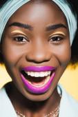 usmívající se africká americká mladá žena s fialovými rty izolované na žluté