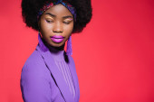 african american young woman in purple stylish outfit isolated on red